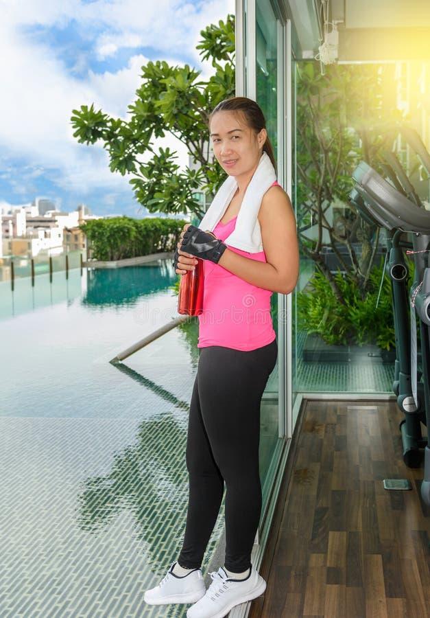 Mujer del gimnasio que resuelve el agua potable en el centro de aptitud foto de archivo