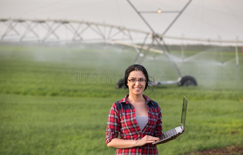 Mujer del granjero delante del sistema de riego foto de archivo
