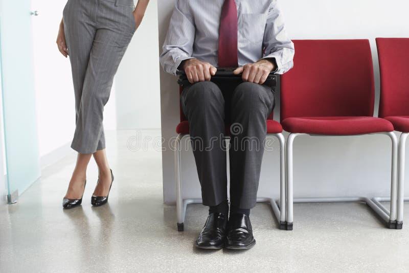 Mujer del hombre con el ordenador portátil en silla en pasillo imagen de archivo