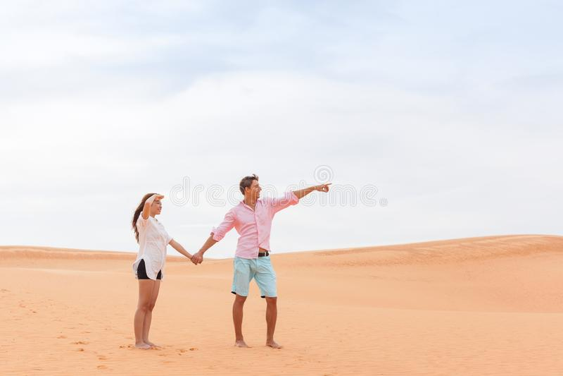 Mujer del hombre joven en muchacha asiática y Guy Point Finger Sand Dune de los pares hermosos del desierto fotos de archivo