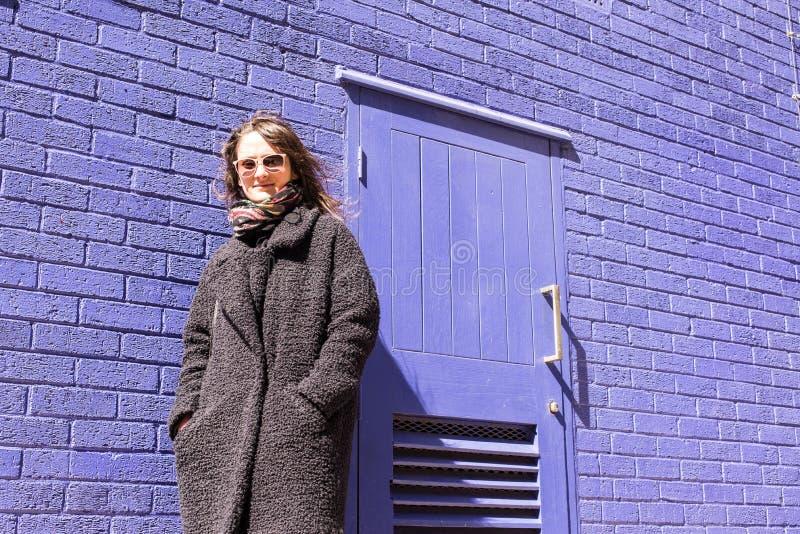 Mujer del inconformista con las gafas de sol que se colocan delante de la pared violeta imagen de archivo