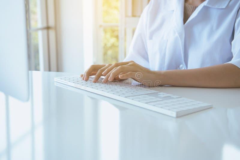 Mujer del investigador de la mano usando el teclado de ordenador en el escritorio en el sitio de la oficina, cierre que mecanogra imagen de archivo