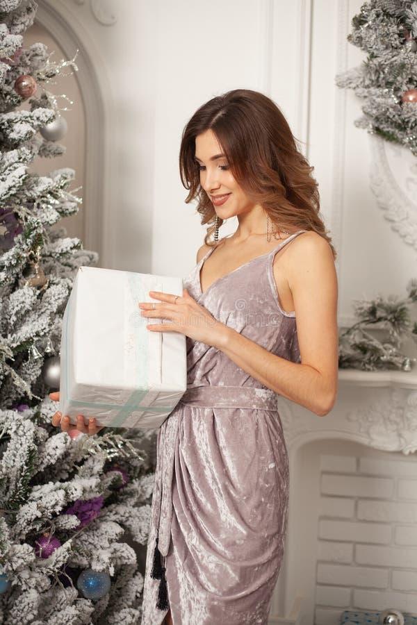 Mujer del invierno de la Navidad que sostiene la caja de regalo mágica de la Navidad Año Nuevo hermoso y árbol de navidad fotografía de archivo libre de regalías