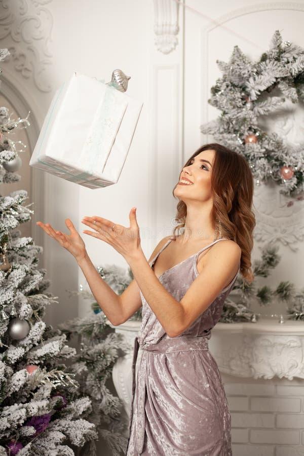 Mujer del invierno de la Navidad que sostiene la caja de regalo mágica de la Navidad Año Nuevo hermoso y árbol de navidad fotografía de archivo