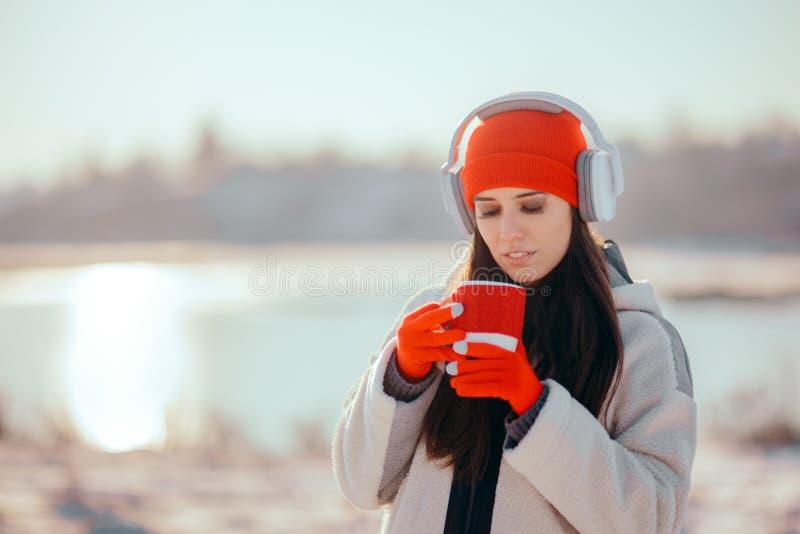 Mujer del invierno que bebe la bebida caliente que escucha la música foto de archivo libre de regalías