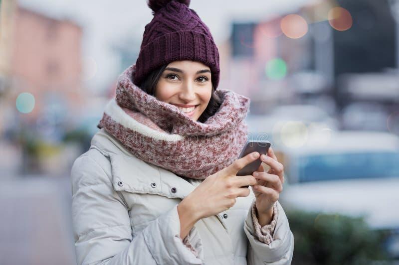 Mujer del invierno que manda un SMS en el teléfono fotografía de archivo libre de regalías
