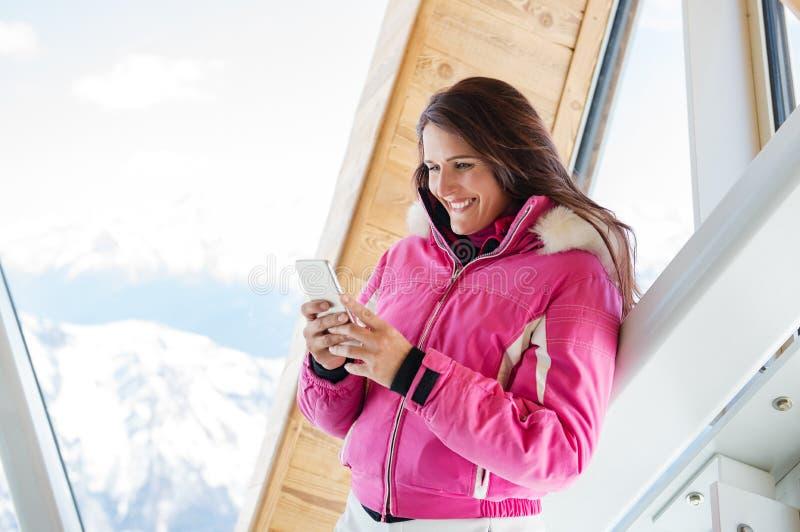 Mujer del invierno que usa el teléfono en casa de campo imagen de archivo