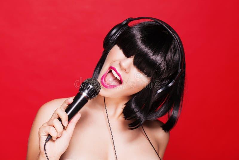 Mujer del Karaoke que escucha la música en los auriculares imágenes de archivo libres de regalías
