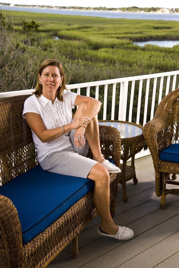 mujer del Mediados de-adulto que se sienta solamente en terraza foto de archivo