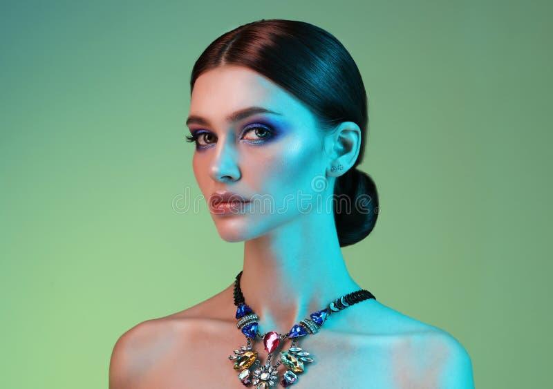 Mujer del modelo de alta moda en las luces brillantes coloridas que presentan en estudio foto de archivo