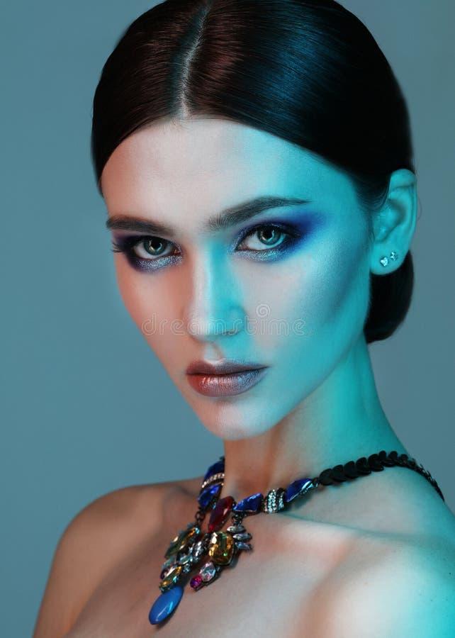Mujer del modelo de alta moda que presenta en estudio Retrato de la joyer?a que lleva de la muchacha atractiva hermosa con maquil imagen de archivo libre de regalías