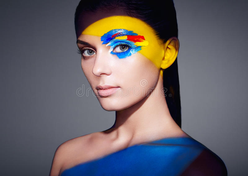 Mujer del modelo de moda con la cara coloreada pintada foto de archivo