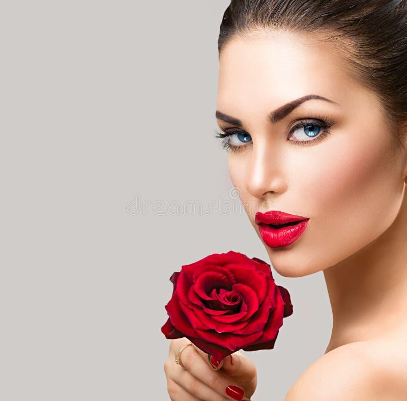 Mujer del modelo de moda de la belleza con la flor de la rosa del rojo imagenes de archivo