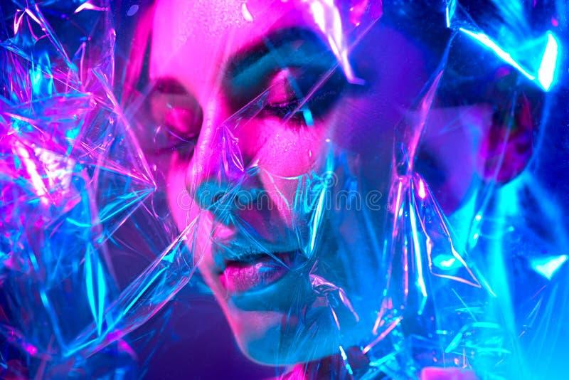 Mujer del modelo de moda en las luces de neón brillantes coloridas que presentan en estudio a través de la película transparente  foto de archivo