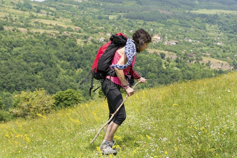 Mujer del montañés con la mochila en un prado con las flores fotos de archivo libres de regalías