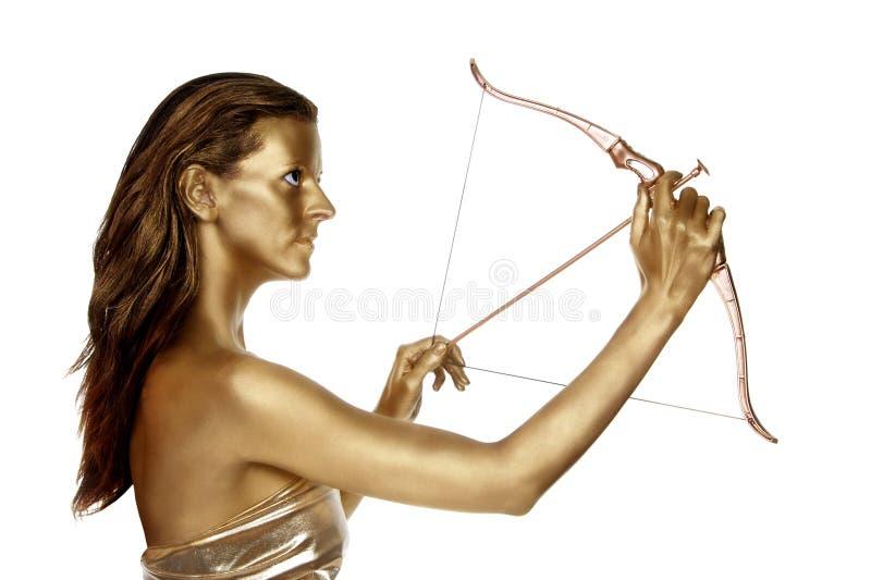Mujer del oro con un arqueamiento y una flecha fotografía de archivo