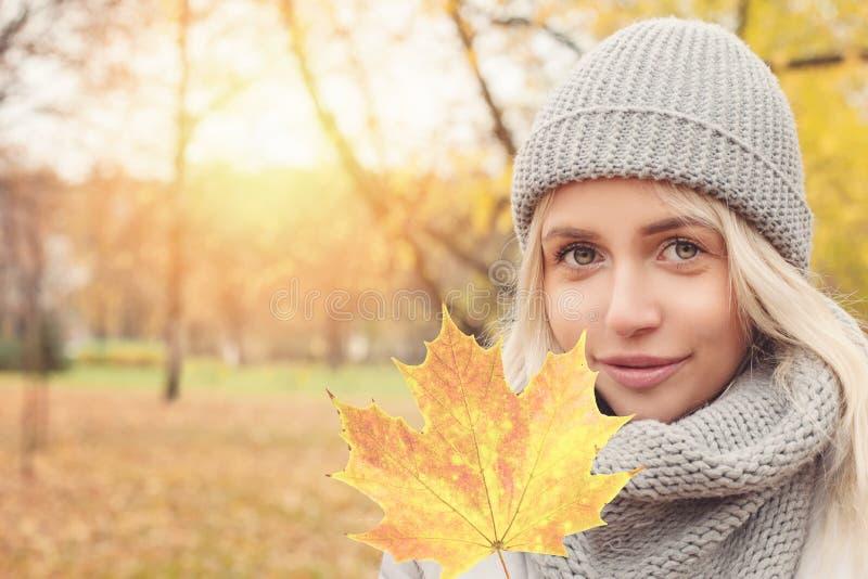 Mujer del otoño con la hoja de arce amarilla al aire libre imagen de archivo libre de regalías