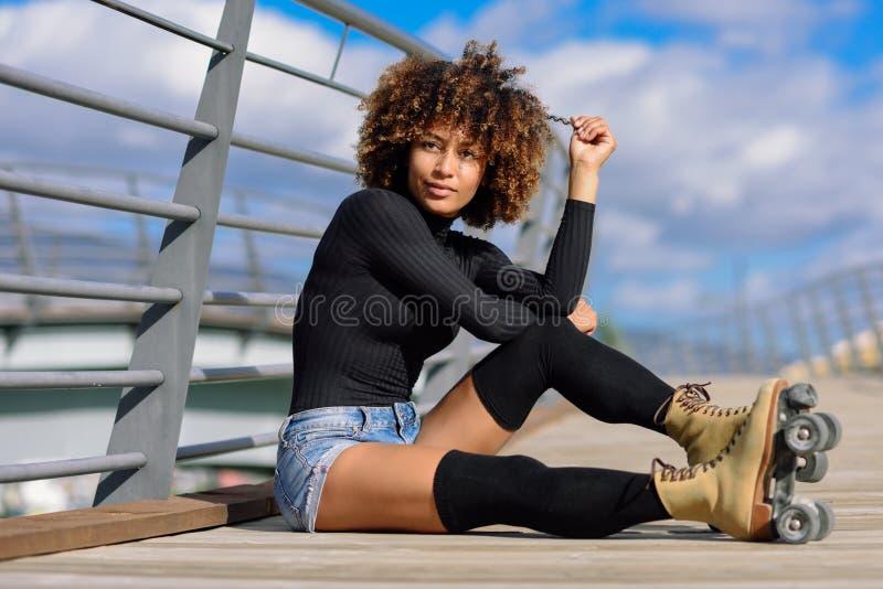 Mujer del peinado del Afro en los pcteres de ruedas que se sientan en el puente urbano fotos de archivo libres de regalías