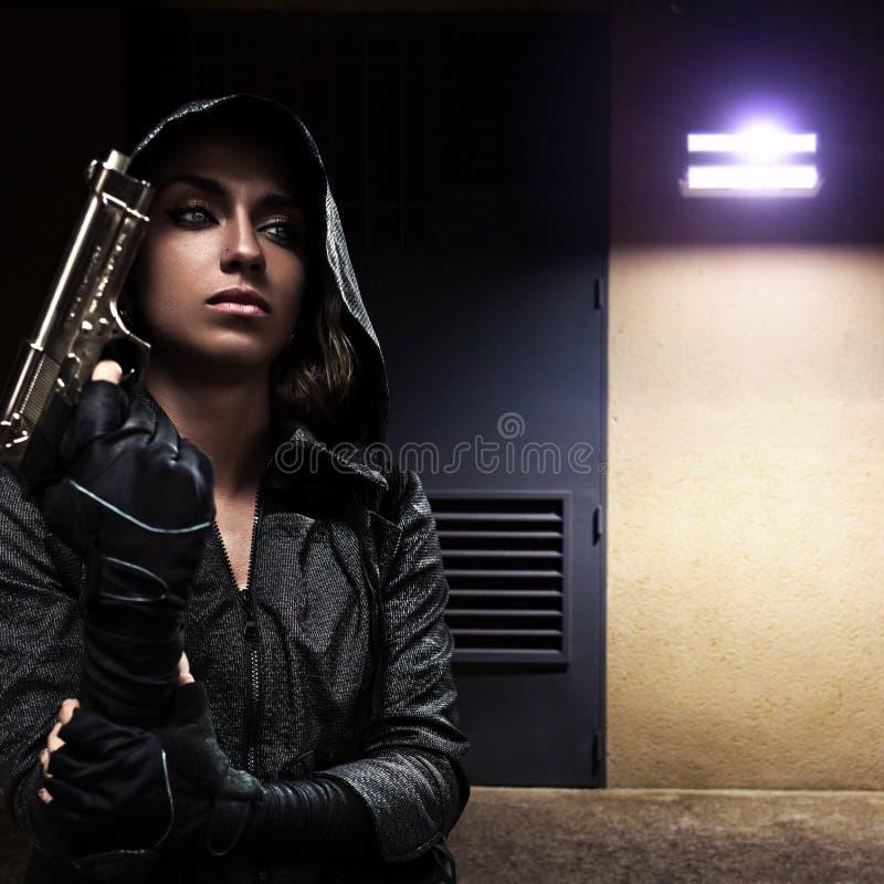 Mujer del peligro con el arma imagenes de archivo
