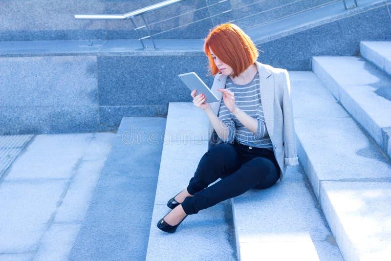 Mujer del pelirrojo del negocio que lee cuidadosamente la tableta foto de archivo libre de regalías