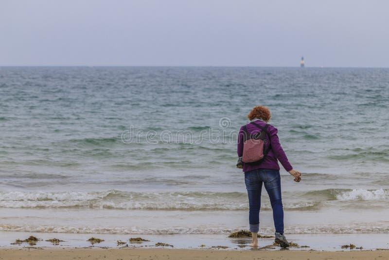 Mujer del pelirrojo en la costa imagenes de archivo