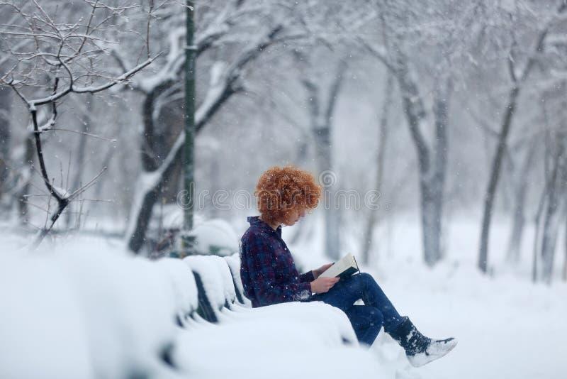 Mujer del pelirrojo que lee un libro en la nieve fotos de archivo