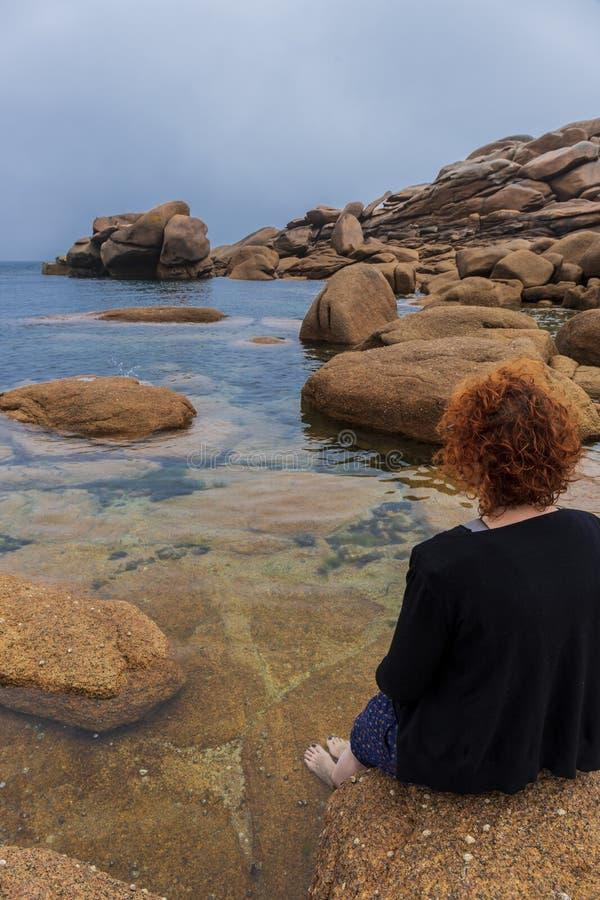 Mujer del pelirrojo que mira el horizonte en la costa fotografía de archivo