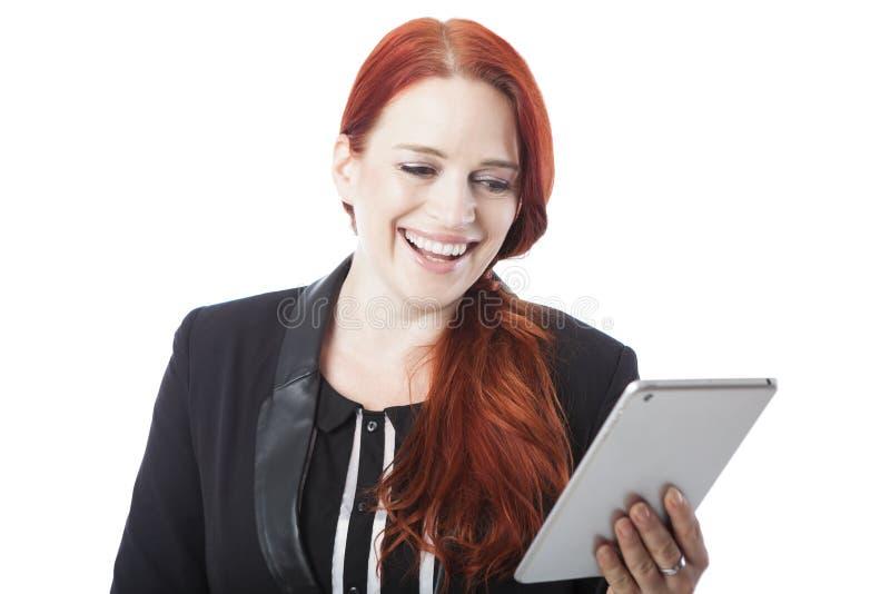 Mujer del pelirrojo que ríe como ella lee su tableta fotos de archivo
