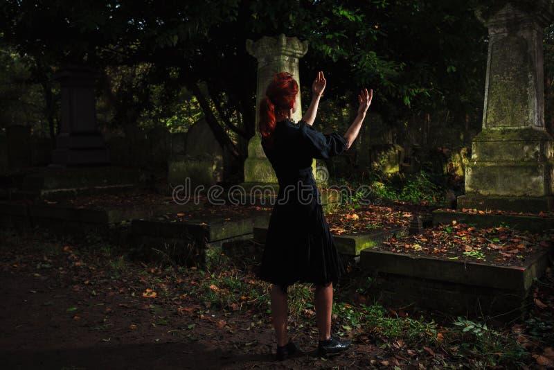 Mujer del pelirrojo que realiza ritual en el sepulcro fotografía de archivo