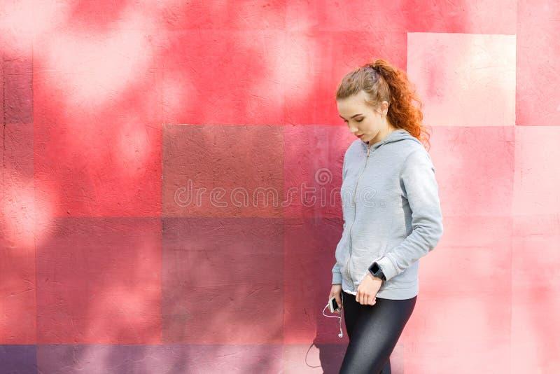 Mujer del pelirrojo que se coloca en la pared brillante fotografía de archivo