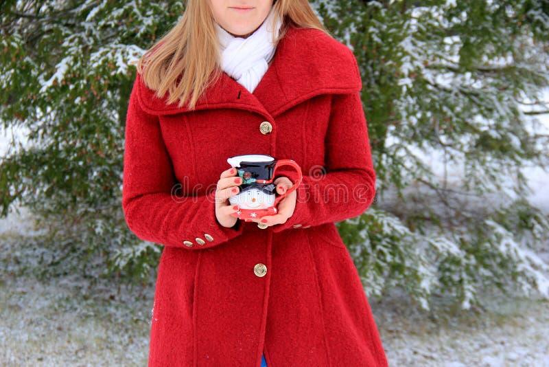 Mujer del pelo bastante rubio hacia fuera en la nieve, sosteniendo la taza linda del día de fiesta con café caliente fotos de archivo libres de regalías
