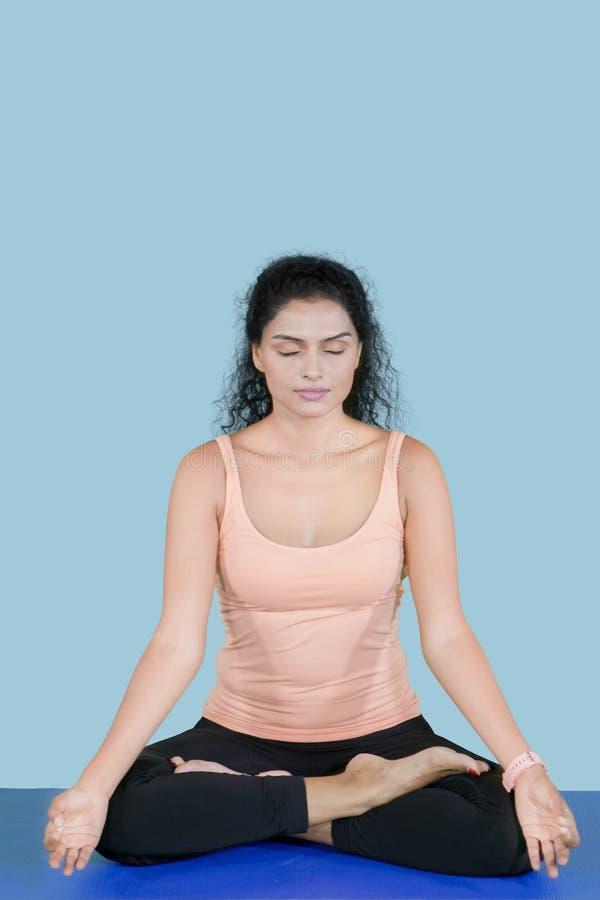 Mujer del pelo rizado que hace la meditación en el estudio imagen de archivo