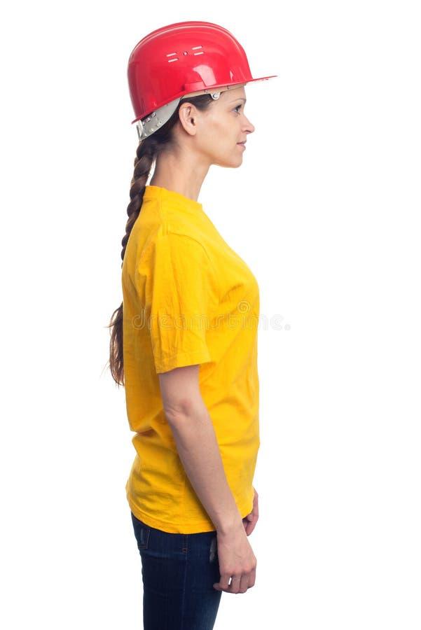 Mujer del perfil con el casco de la construcción Aislado foto de archivo
