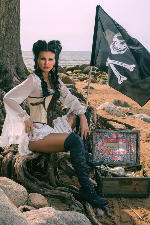 Mujer del pirata que se sienta cerca de cofre del tesoro fotografía de archivo