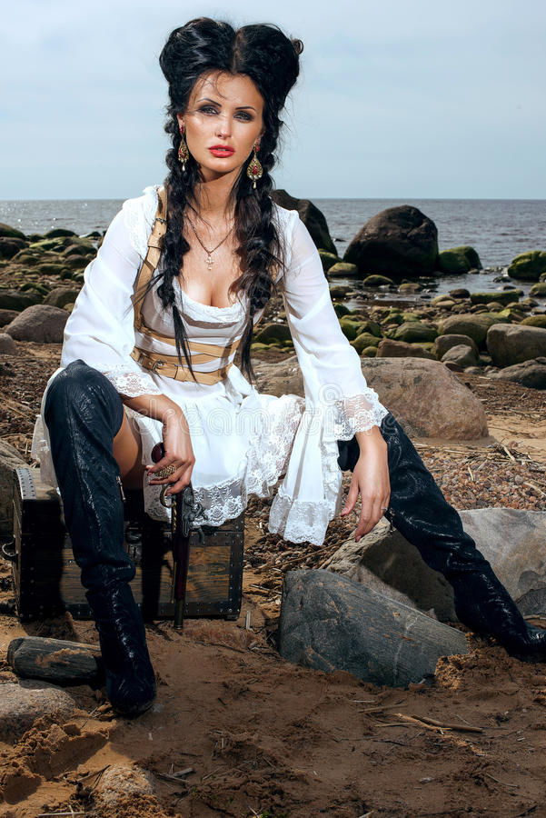 Mujer del pirata que se sienta cerca de cofre del tesoro foto de archivo