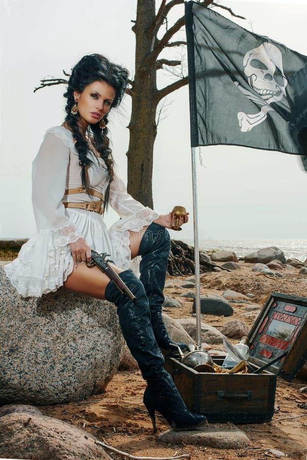 Mujer del pirata que se sienta cerca de cofre del tesoro foto de archivo libre de regalías