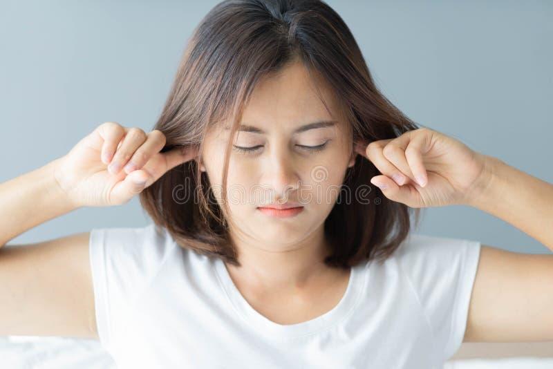 Mujer del primer que cubre los oídos con su mano, problema de ruido, foco selectivo fotos de archivo libres de regalías
