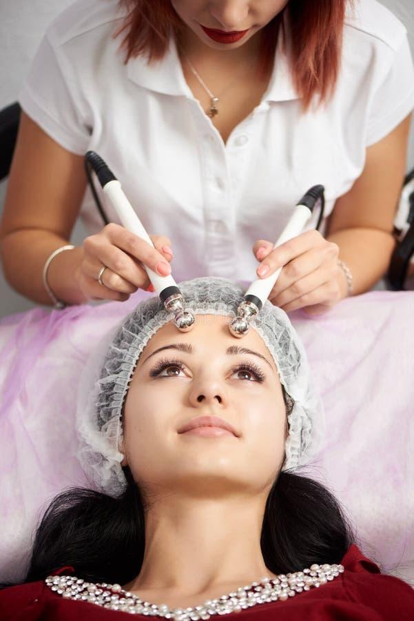 Mujer del primer que recibe el tratamiento microcurrent facial de terapeuta en el salón imágenes de archivo libres de regalías