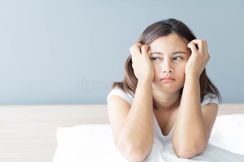 Mujer del primer que se sienta en cama en el dormitorio con el pensamiento o la sensación deprimida, foco selectivo fotografía de archivo libre de regalías