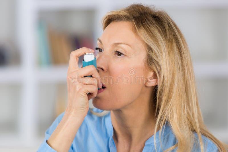 Mujer del primer que usa el inhalador del asma en sala de estar imagen de archivo