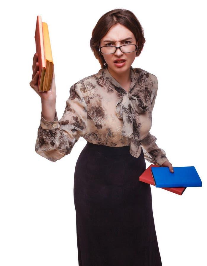 Mujer del profesor de la muchacha enojada en vidrios con los libros aislados en blanco imágenes de archivo libres de regalías