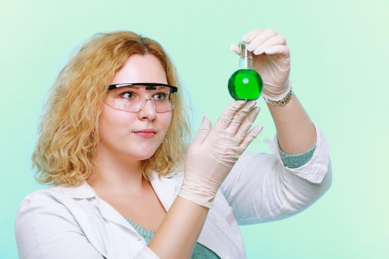 Mujer del químico con el frasco químico de la cristalería foto de archivo libre de regalías