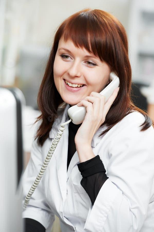 Mujer del químico de la farmacia en droguería con el teléfono foto de archivo