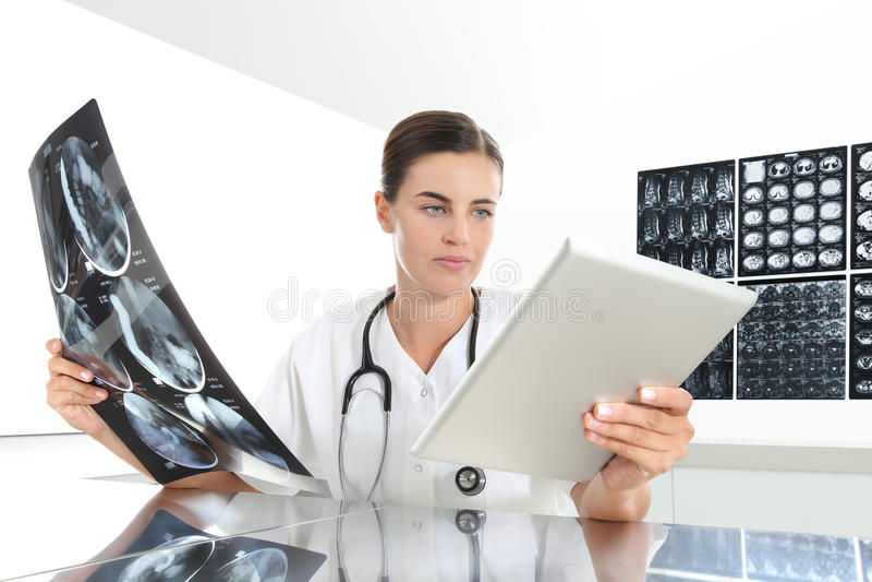 Mujer del radiólogo que comprueba la radiografía, con la tableta, atención sanitaria fotos de archivo