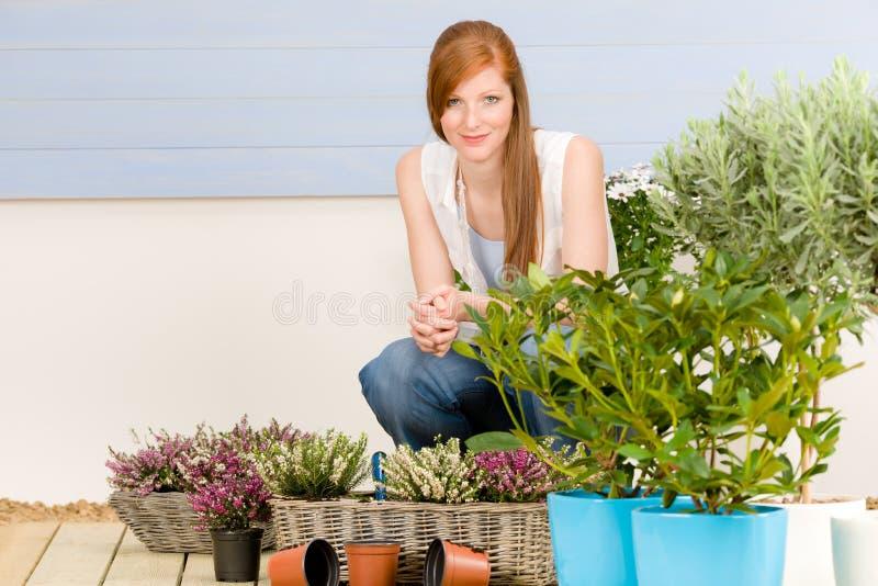 Mujer del redhead de la terraza del jardín del verano con las flores foto de archivo