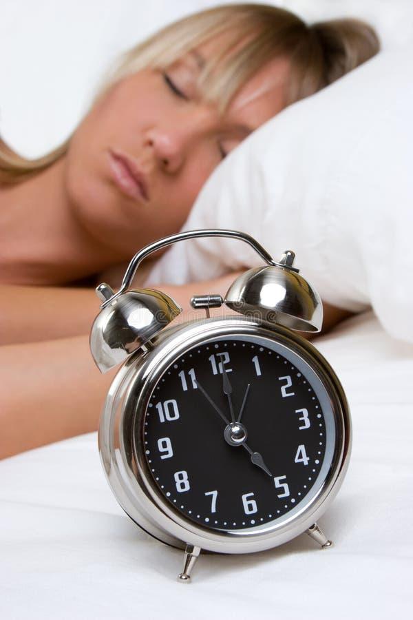 Mujer del reloj de alarma foto de archivo libre de regalías