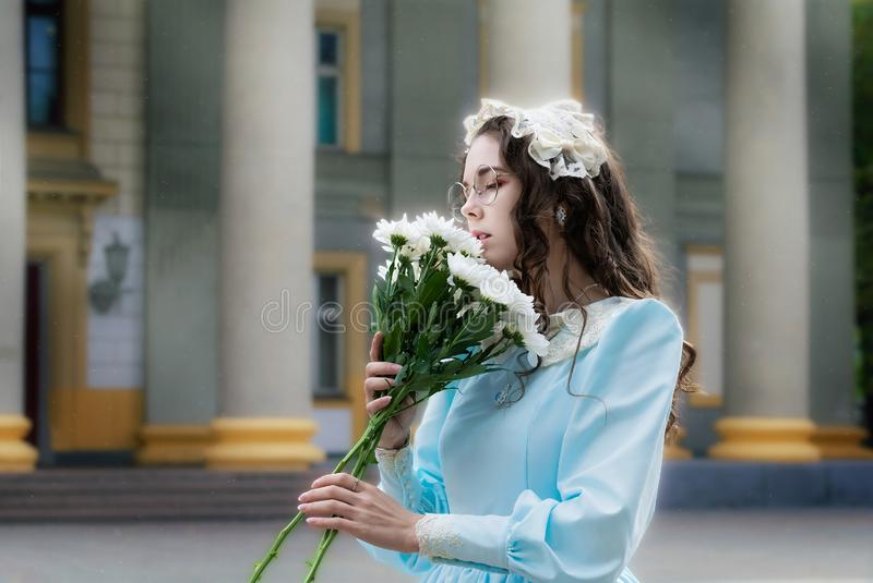 Mujer del retrato con un ramo de crisantemos blancos fotografía de archivo