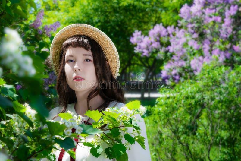 Mujer del retrato en el vestido blanco cerca del espino floreciente imagenes de archivo