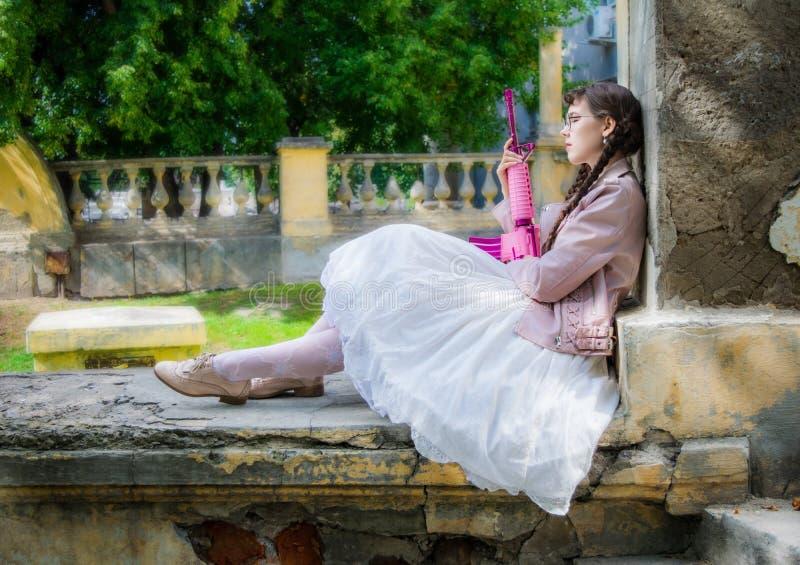 Mujer del sueño con una reclinación rosada del rifle imagenes de archivo
