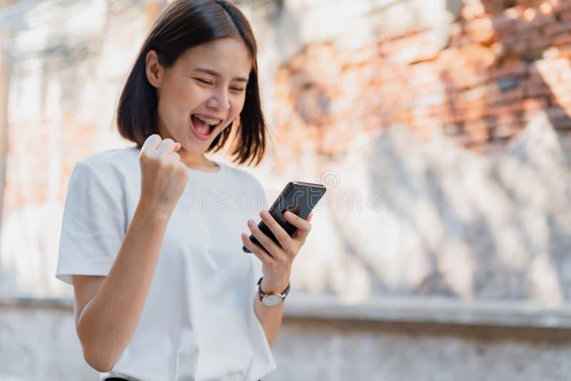 Mujer del teléfono elegante sonriente y que se considera feliz con sorprendido para el éxito imágenes de archivo libres de regalías
